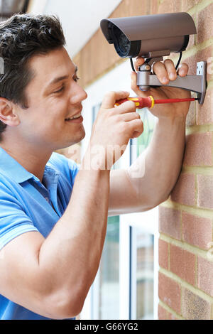Security Consultant Fitting Security Camera To House Wall - Stock Photo