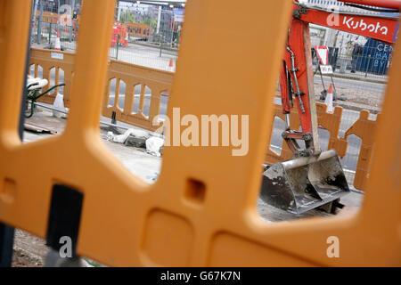 Kubota digger bucket and arm at roadworks site. - Stock Photo