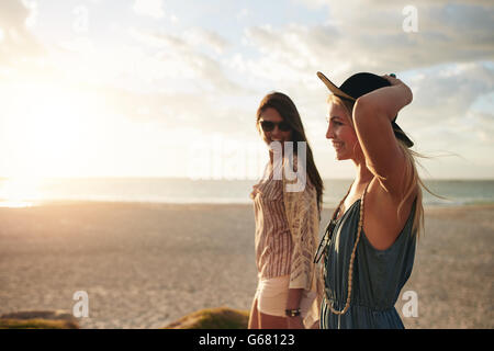 Happy young women walk along coastline on a sunny day. Best friends walking together on a beach, enjoying summer - Stock Photo
