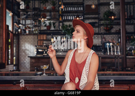 Portrait of attractive young woman smoking in a bar. Holding cigarette and looking away. - Stock Photo