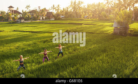 Fitness woman doing yoga in farm outdoors. Yoga class in farm lands. - Stock Photo
