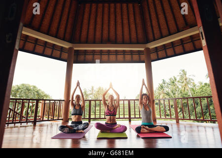 Three young women practicing yoga in a gym sitting cross legged on their mats and meditating. Group of people doing - Stock Photo