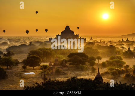 Scenic sunrise with hot air balloons above Bagan in Myanmar. Bagan is an ancient city with thousands of historic - Stock Photo