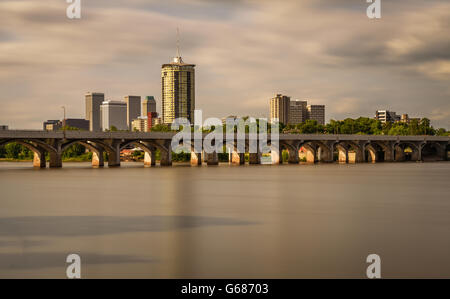 Sunset skyline of Tulsa, Oklahoma with Arkansas river in the foreground. Long exposure. - Stock Photo