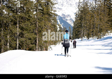 A woman is cross country skiing in Austria - Stock Photo
