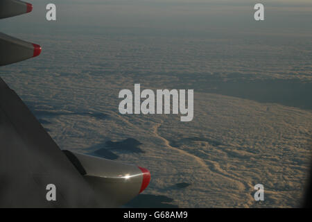 A sea of clouds, with mountains peaking over the cloud base. Taken from an aircraft - Stock Photo