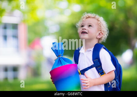Happy child holding traditional German candy cone on first school day. Little student with books excited to be back - Stock Photo