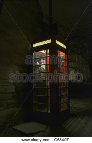 Traditional red telephone box at night - Stock Photo
