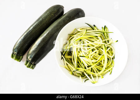 Two zucchini or courgettes with some spiralized for pasta substitute in a white bowl on white background - Stock Photo