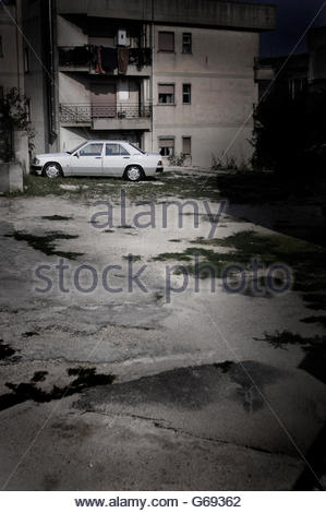 Parked white car by apartment block - Stock Photo