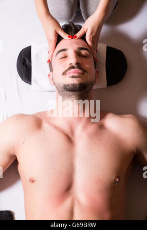 A young masseuse applying a head massage to a young male. - Stock Photo