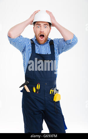 Astonished shocked young builder in helmet staning with mouth opened - Stock Photo