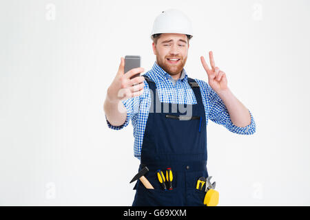 Smiling handsome young builder showing peace sign and making selfie with mobile phone - Stock Photo