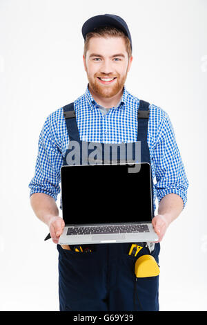 Happy young builder in overall and cap holding blank screen laptop - Stock Photo