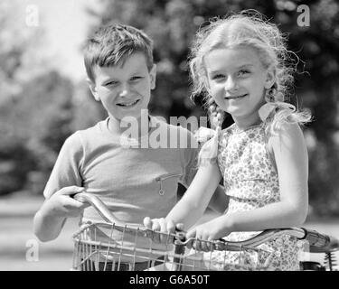 1930s 1940s PORTRAIT SMILING BOY PUSHING BIKE WITH BLOND GIRL PIGTAILS SITTING BY HANDLEBARS BOTH LOOKING AT CAMERA - Stock Photo