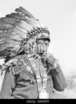 1930s NATIVE AMERICAN MAN CHIEF WEARING FULL FEATHERED HEADDRESS BEADED COSTUME SANTA CLARA PUEBLO NEW MEXICO USA - Stock Photo