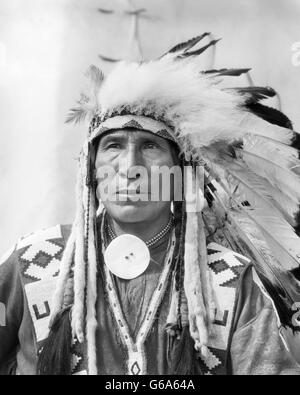 1920s PORTRAIT NATIVE AMERICAN INDIAN MAN CHIEF SITTING EAGLE IN FULL HEADDRESS STONEY TRIBE OF BANFF ALBERTA CANADA - Stock Photo