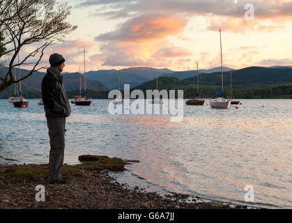 Mature male hiker looking out over Ullswater at sunset. Pooley Bridge, Lake District national park, Cumbria, England, - Stock Photo