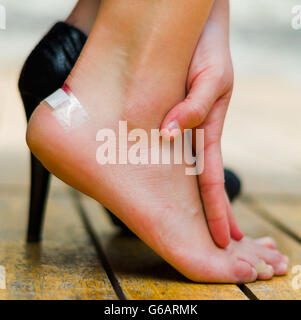 Injured foot because of high heels, little white patch on ankle. Hand making massage - Stock Photo