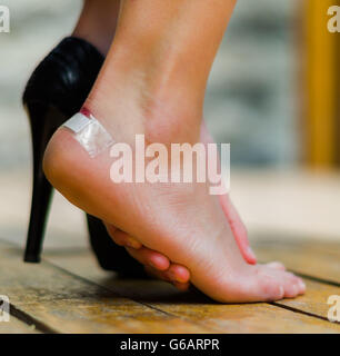 After using high heels for long time, foot are tired. Hand making some massage, white little patch on ankle - Stock Photo
