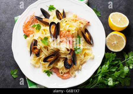 Pasta with seafood on stone table. Mussels and prawns. Top view - Stock Photo