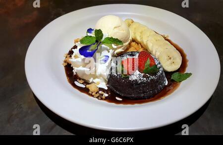 Chocolate fondant lava cake decorated with sprinkling of icing sugar, fresh strawberries, banana and ice cream - Stock Photo
