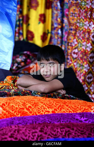 Uzbeki fabric vendor, Urgut market, Samarkand, Uzbekistan - Stock Photo
