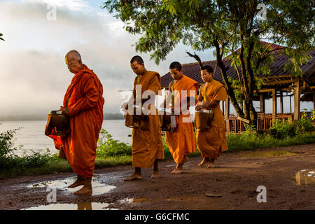 Buddhist Monks during Morning Alms Giving on Don Khong Island in Southern Laos - Stock Photo