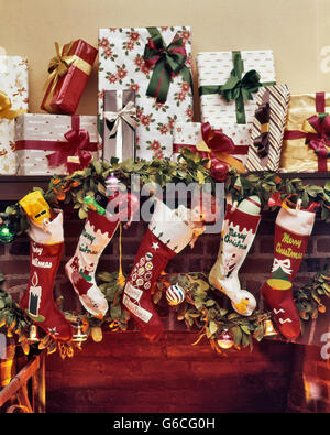 1960s FIVE CHRISTMAS STOCKINGS HANGING ON FIREPLACE MANTLE LOTS OF WRAPPED PRESENTS STACKED ABOVE - Stock Photo