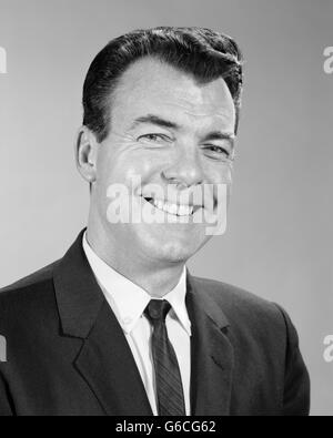 1960s SMILING BUSINESS MAN PORTRAIT WEARING SUIT TIE LOOKING AT CAMERA - Stock Photo
