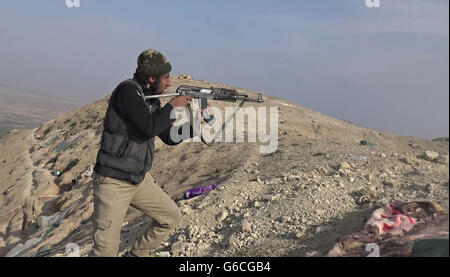 Islamic State fighter fires an Ak-47 during fighting in the Makhoul Mountains May 30, 2016 near Baiji, Iraq. The - Stock Photo