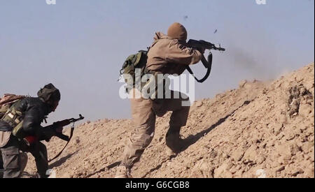 Islamic State fighters fire AK-47 rifles during fighting in the Makhoul Mountains May 30, 2016 near Baiji, Iraq. - Stock Photo