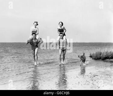 1930s TWO COUPLES RUNNING IN OCEAN WEARING BATHING SUITS GIRLS SITTING ON BOYS SHOULDERS AND DOG RUNNING ALONG SIDE - Stock Photo