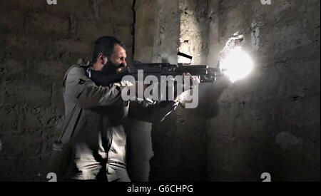 Islamic State fighter fires an automatic weapon during urban fighting April 4, 2016 in the vicinity of Zawbaa, Iraq. - Stock Photo
