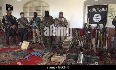 Islamic State fighters pose with captured weapons after over running an Iraqi outpost April 4, 2016 in the vicinity - Stock Photo
