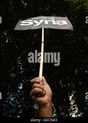 An activist holds a placard during an event organised by Stop the War Coalition to protest against potential UK involvement in the Syrian conflict in Whitehall, London.