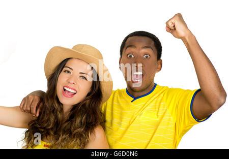 Charming interracial couple wearing yellow football shirts cheering joyfully to camera, white studio background - Stock Photo