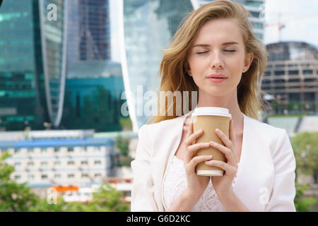 business woman blonde holding coffee outdoors on city background - Stock Photo