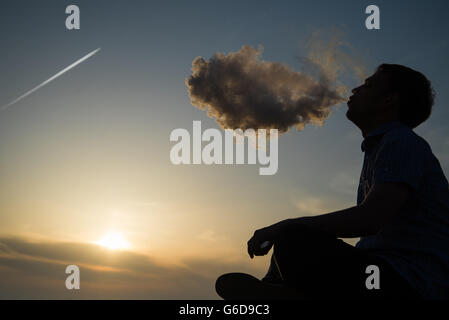 Silhouette of man smoking a pipe in cap at sunset. Photographer in a baseball cap smoking a pipe at sunset by the - Stock Photo