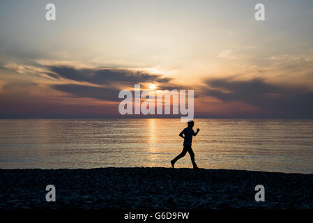 Male runner silhouette on the beach - Stock Photo