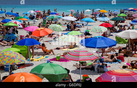 People and Sunshades on Stintino Beach Sardinia Italy - Stock Photo