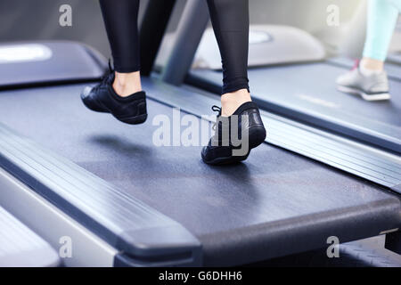 Close up of female legs on tredmill - Stock Photo