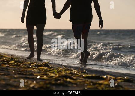 A couple walking hand in hand along on a tropical beach - Stock Photo