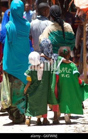 Ethiopian schoolchildren arm in arm  together in the street, Harar, Ethiopia - Stock Photo
