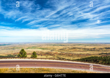 View of a highway with a beautiful landscape and dramatic sky near Sheridan, Wyoming - Stock Photo