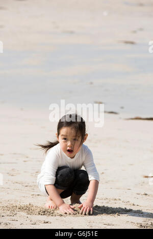 Cute Asian Girl Playing With Sand on the Beach - Stock Photo