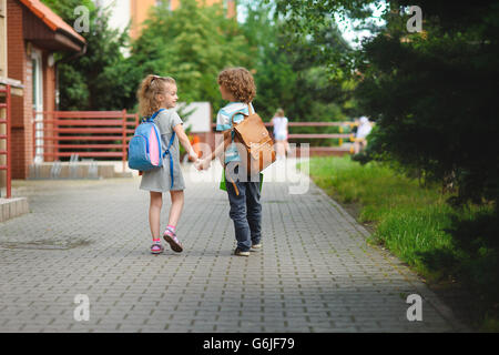 Back to school. Two young students go to school hand in hand. They about something briskly talk. Behind the back - Stock Photo