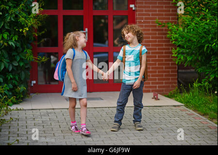 Little school students go on a schoolyard holding hands. Children with a smile look at each other. Boy and girl. - Stock Photo