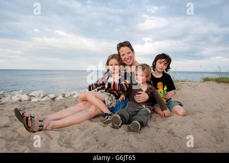 Mother and children sitting together on beach, portrait - Stock Photo