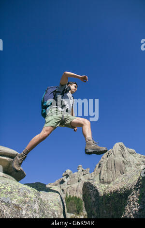 Spain, hiker with backpack jumping on the rocks in La Pedriza - Stock Photo